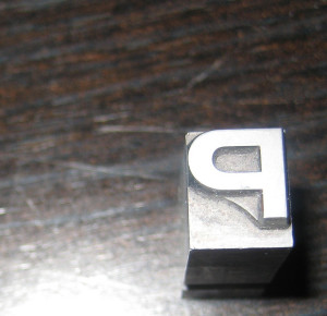 Trykkplate med bokstaven P illustrerer grafisk ferdiggjøring.